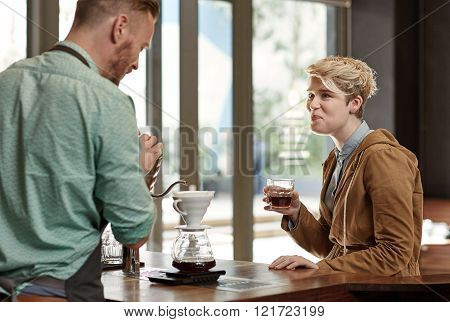 Friendly barista busy pouring a fresh cup of filter coffee while chatting to a regular young woman customer, who is enjoying a glass of filter coffee on a work break
