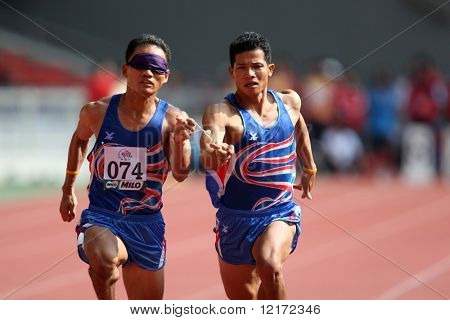 KUALA LUMPUR - AUGUST 15: Thailand's blind athlete Kitsana Jorchuy runs with a guide at the track and field event of the fifth ASEAN Para Games on August 15, 2009 in Kuala Lumpur.