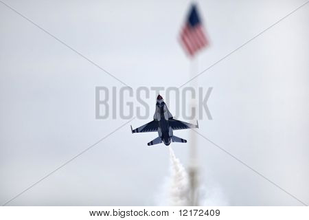 SUBANG, MALAYSIA - OCTOBER 3: USAF Thunderbirds F-16 plane flying past the US flag in an air show over the skies of the Subang Air Force Base. October 3, 2009 in Subang Malaysia.