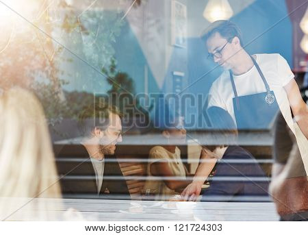 Waiter serving a couple their pastries in a busy modern cafe, as seen through the cafe window