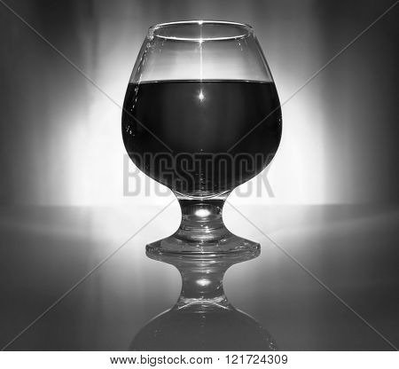 wineglass of alcoholic beverage on a glass table