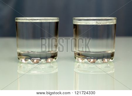 two glasses filled with vodka standing on a glass table