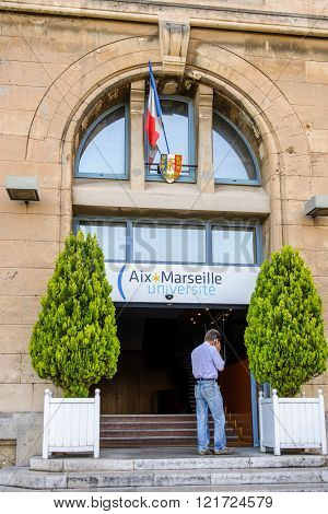 MARSEILLE FRANCE - JUL 18 2014: Man speaking on mobile phone at the entrance of the Aix Marseille University in the city of Marseille France. Aix-Marseille University is a public research university located in Provence southern France. It was founded in 1