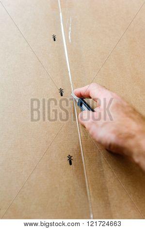 Man cutting a cardboard box sharp steel box cutter knife to open it. ** Note: Shallow depth of field