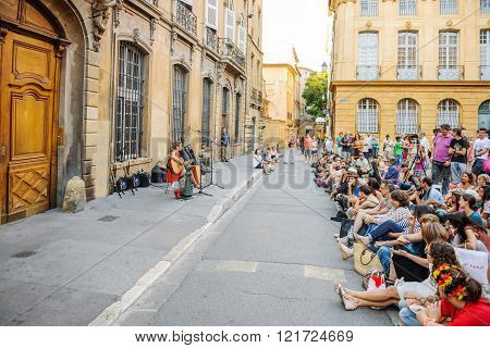 AIX-EN-PROVENCE FRANCE - JUL 17 2014: Woman singing on a guitar being admired by tens of people on the streets of Aix-En Provence on a summer warm day