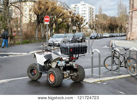 STRASBOURG FRANCE - FEB 9 2016: AEON ATV All terrain vehicle parked near a bike in the center of the city of Strasbourg.