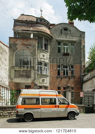 BRASOV ROMANIA - JUL 5 2016: Old Red Cross van in front of an old vintage house - headquarter of the central branch of Old Cross Romania - Old City of Brasov Romania