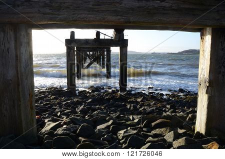 A view of crashing waves under the old wooden pier at Aberdour