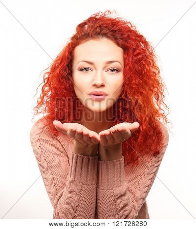 Red-haired young woman giving air kiss, isolated on white