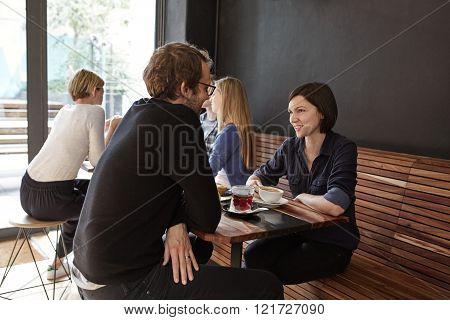 Young woman smiling at her boyfriend in a modern and stylish cafe with other customers in the background