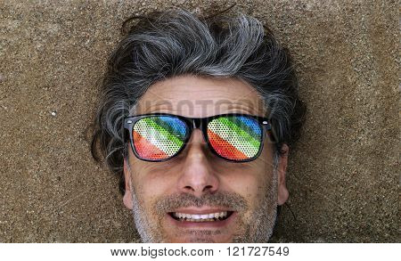 man with grey hairs laying on sandy beach