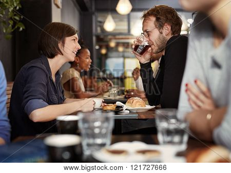 Busy cafe with a young couple on a coffee date at a table among other customers, with the woman talking as her boyfriend sips his coffee