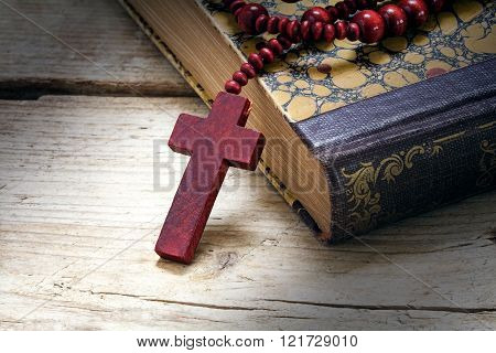 catholic wooden rosary beads with cross on an old book on rustic wood, religious symbol concept