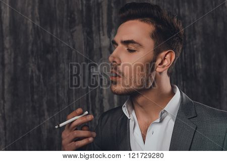Side View Of A Cheeky Man In Suit On The Grey Background Smoking A Cigarette