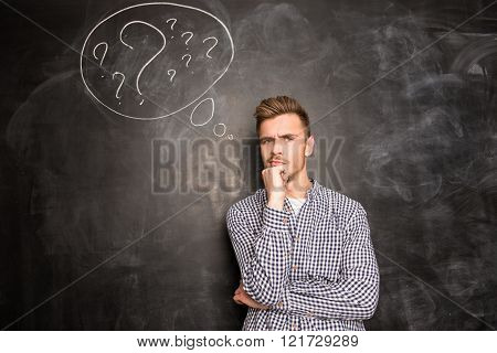 Young Man Against The Background Of Chalkboard Thinking About The Problem
