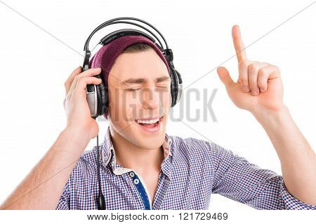 Man In Cap And Headphones Listening Music And Gesturing With Raised Finger