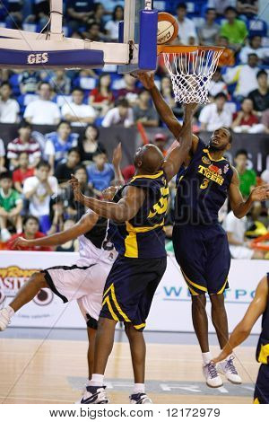 KUALA LUMPUR - DECEMBER 13: KL Dragons' Guga (L) sneaked the ball in between the hands of the Thailand Tigers' I. Nwankwo(C) and C. Briggs (R) in the ABL match on December 13, 2009 in Kuala Lumpur.