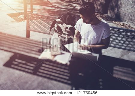 Young man wearing white tshirt sitting city park and reading book. Studying at the University, prepa