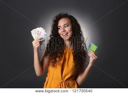 Beautiful young girl holding credit cards and cash on grey background