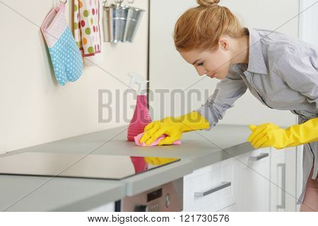 Young woman scrubbing the kitchen counter with a rag