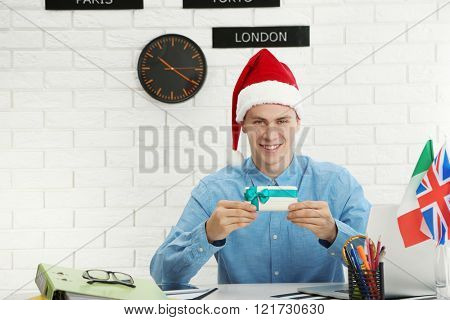 Young man with Santa hat showing gift box in the office of travel company