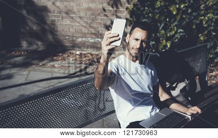 Photo man sitting city park bench and making selfie smartphone. Using wireless internet. Studying at