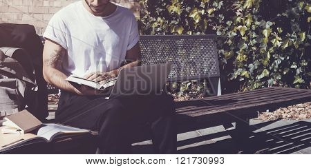 Stylish man wearing white tshirt sitting city park and reading book. Studying at the University, wor