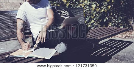 Man wearing white tshirt sitting city park and writes message. Studying at the University, working p