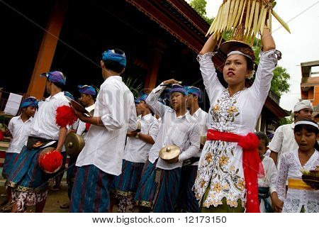 BALI - JANUARY 14: Team of musicians and a Balinese woman with offering of food basket on her head in a procession January 14, 2010 in Bali, Indonesia.