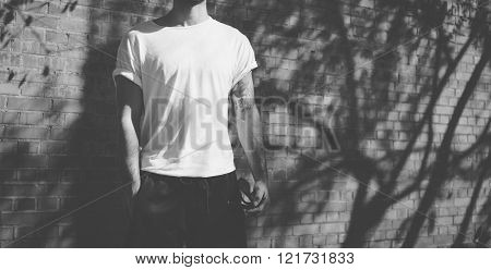 Photo young hipster with tattoo wearing blank white tshirt. Stands in front of a brick wall. City st