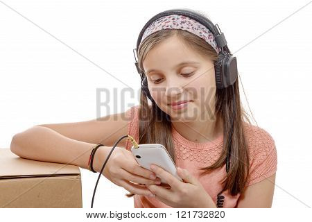 a preteen girl listening to music with his smartphone, on white