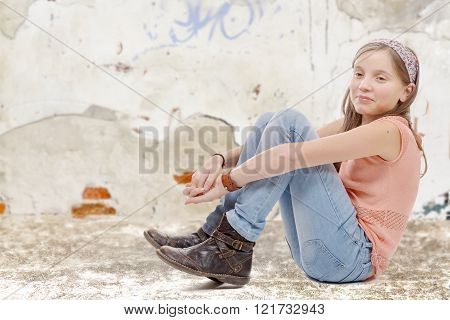 a young preteen sitting on the floor