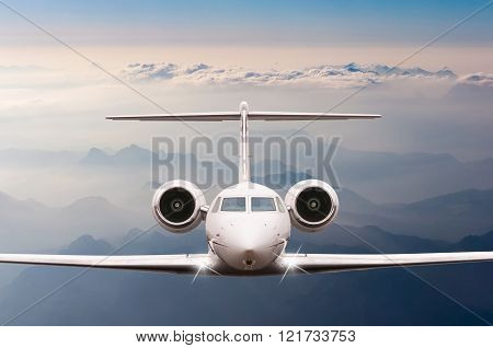 Private Airplane fly over clouds and Alps mountain on sunset. Front view of a big passenger or cargo