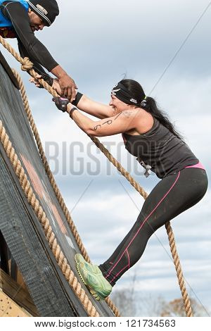 BUFORD, GA - NOVEMBER 2015:  A woman struggles to climb up a wall obstacle using a rope at the Muddy Brute Challenge in Buford, GA on November 21, 2015.