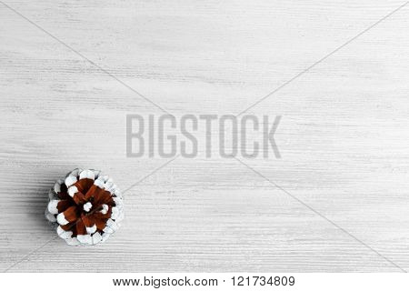 Beautiful simple winter background with pine cone on wooden texture