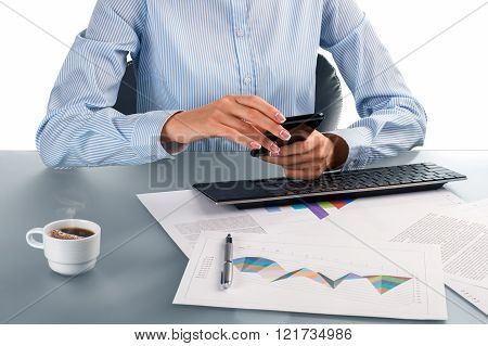 Businesswoman using smartphone at workplace.