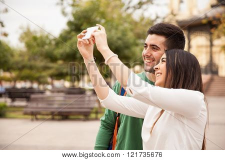 Cute couple taking pictures outdoors
