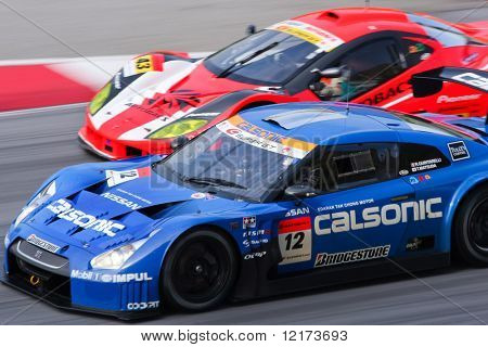 SEPANG, MALAYSIA - JUNE 21: The Calsonic Impul GT-R Nissan car (12) overtaking another car at the Super GT International Series Round 4 race. June 21, 2010 in Sepang Malaysia.
