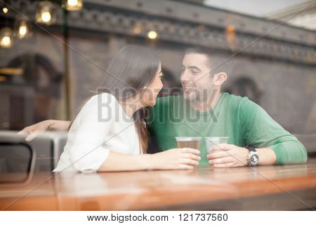 Guy drinking beer with his girlfriend at a bar