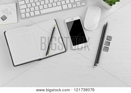 Workplace with mobile phone, computer peripherals and stationery on light table