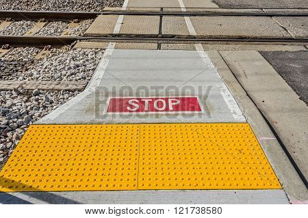 Stop sign on sidewalk with yellow section to keep pedestrians a safe distance from high speed commuter trains.