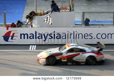 SEPANG, MALAYSIA - JUNE 21: The Up Start Mola Z car (46) taking the checkered flag at the end of the race at the Super GT Round 4 race. June 21, 2010 in Sepang Malaysia.
