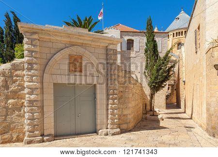 Narrow street between ancient walls and convent of San Francisco in Old City of Jerusalem, israel.