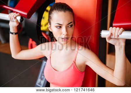 Portrait of attractive young sportswoman training arms muscles in gym