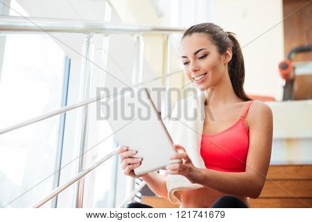 Happy cute young sportswoman sitting and using tablet in gym