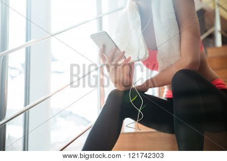 Closeup of sportswoman with white towel sitting and using smartphone with earphones in gym