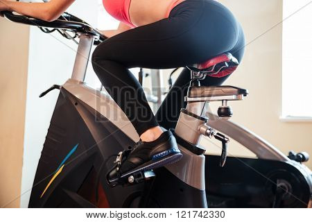Back view of attractive young woman athlete training in gym using bicyle
