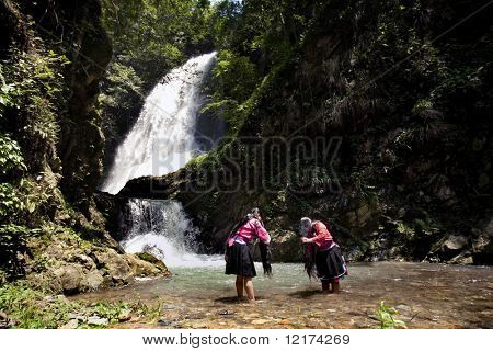 LONGJI, CHINA - MAY 24: Two Yao ladies wash their long hair at the waterfalls on May 24, 2010 in Longji. Keeping long hair is a traditional practice and a sign of beauty to the Yao ethnic minority girls.