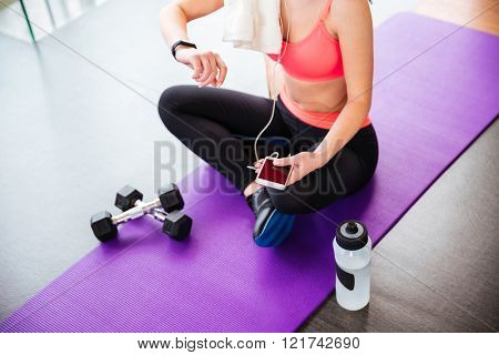 Attractive young sportswoman sitting and using fitness tracker and smartphone on mat in gym