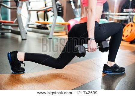 Attractive young woman athlete doing squats with dumbbells in gym
